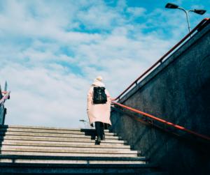 Seniorin beim Treppen steigen mit Arthrose: abnehmen hilft