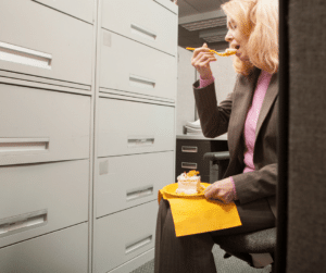 Frau nascht während ihrer Arthritis-Diät im Büro